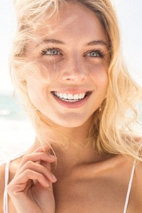 A woman smiling on the beach.