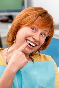 Senior woman pointing to beautiful smile