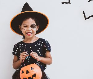 girl in costume holding pumpkin