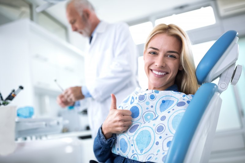 A woman smiling while visiting a dentist in Beachwood.